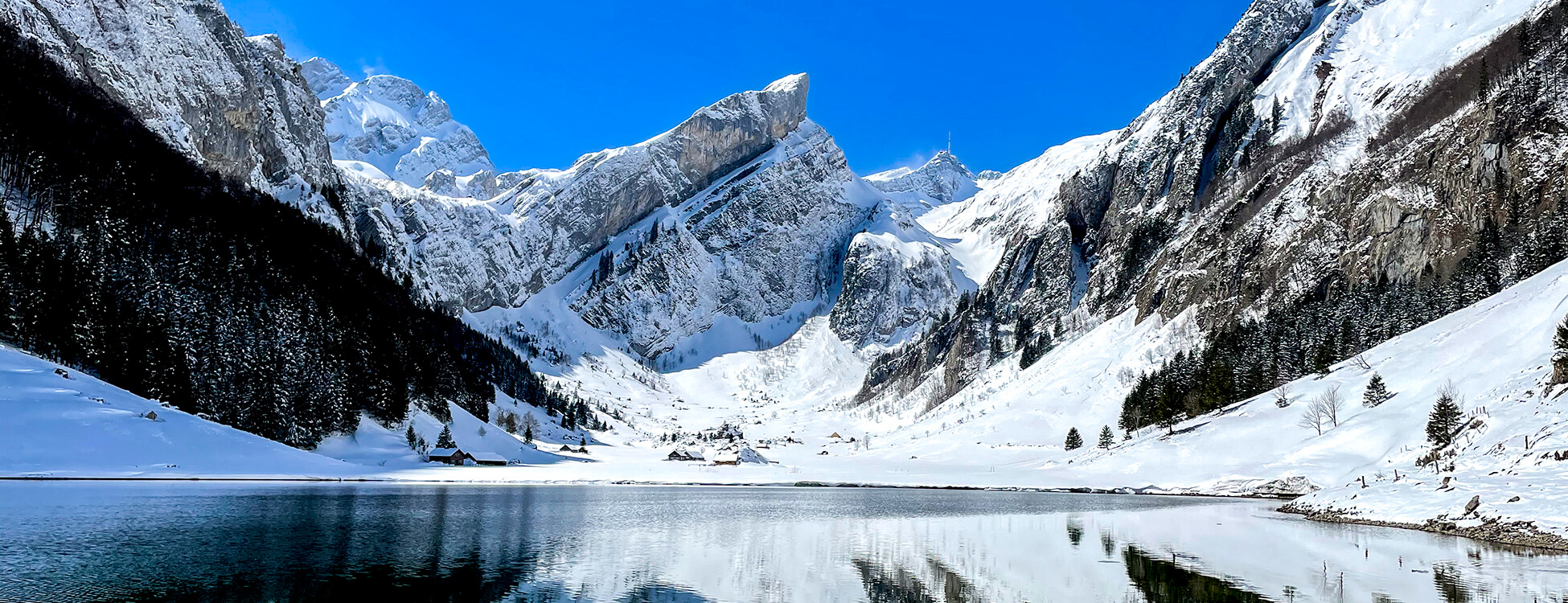 mountain lake with snow on the tips